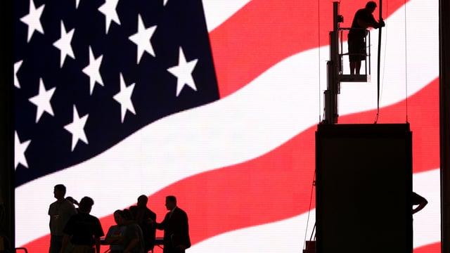 Riesige US-Flagge, davor die Silhouetten von Menschen