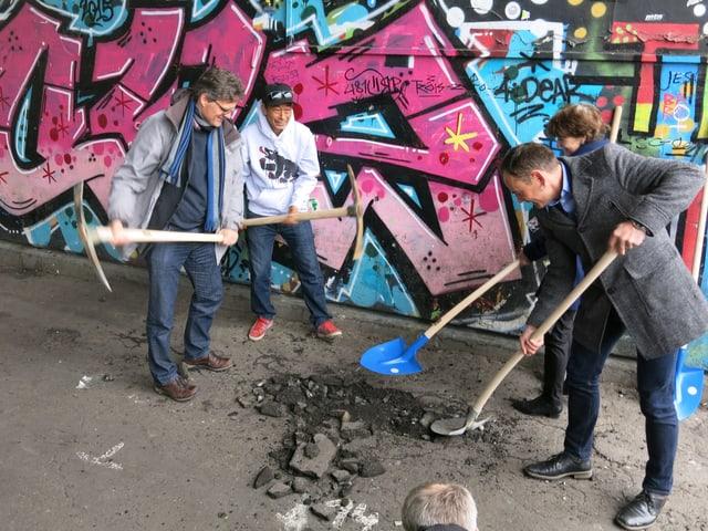Die vier mit Pickeln und Schaufeln vor einer versprayten Wand.