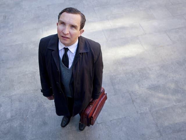 Ein Mann mittleren Alters mit Krawatte und Aktentasche in der Hand steht auf einem Platz und guckt nachoben.