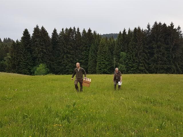 Zwei Männer laufen durch eine Wiese