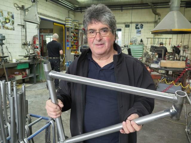 Mann mit grauen Haaren in Werkstatt, hält Rahmen in der Hand.