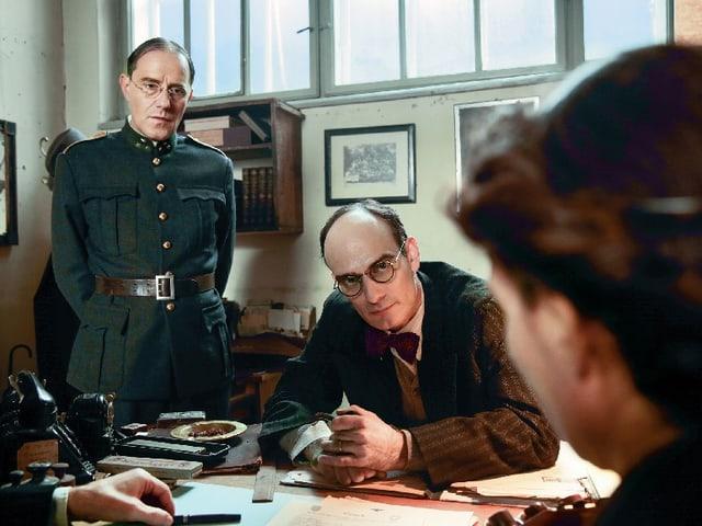 Links steht ein Mann in Uniform. In der Mitte sitzt ein Mann mit Brille und Anzug am Tisch. Rechts ist der Hinterkopf einer Frau zu sehen.