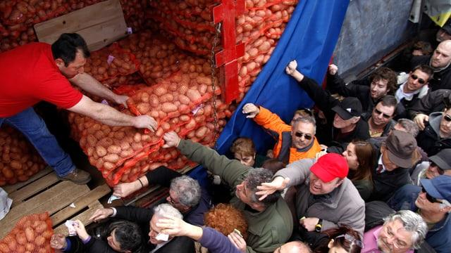 Leute verkaufen Kartoffeln von einem Lastwagen an Personen, die anstehen.