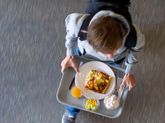 Schüler trägt Tablett mit Mittagessen