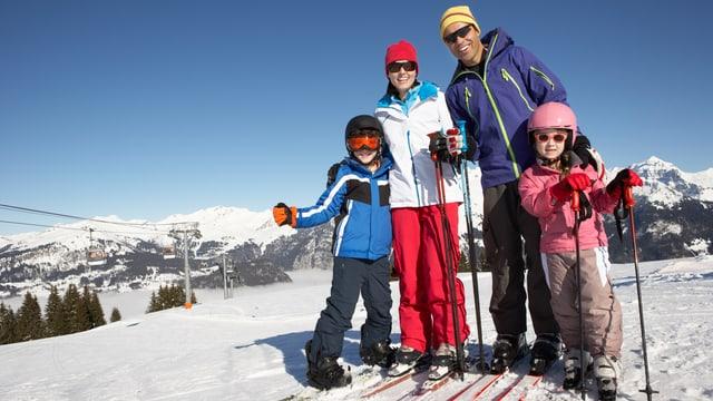 Mutter, Vater und zwei Kinder in Winterausrüstung auf den Skiern an einem strahlenden Wintertag.