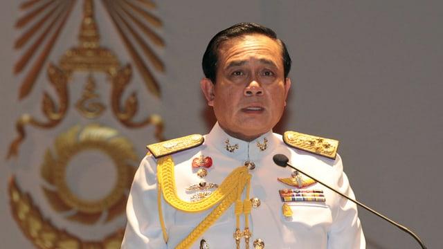 Ein Mann in einer weissen Militäruniform steht an einem Mikrofon.