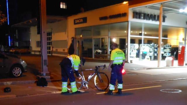 Zwei Kantonspolizisten untersuchen ein Fahrrad, ein Velohelm liegt daneben am Boden.