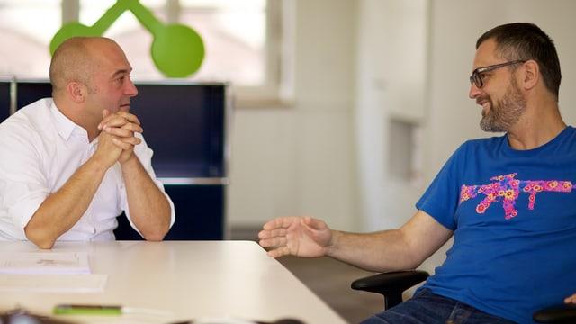 Zwei Männer unterhalten sich am Tisch
