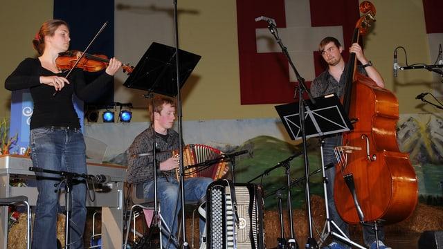 Eine Musikantin mit Geige, ein Musikant am Schwyzerörgeli und der dritte Musikant am Bass.