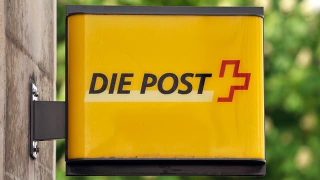 Gelbes Postschild an Hauswand montiert