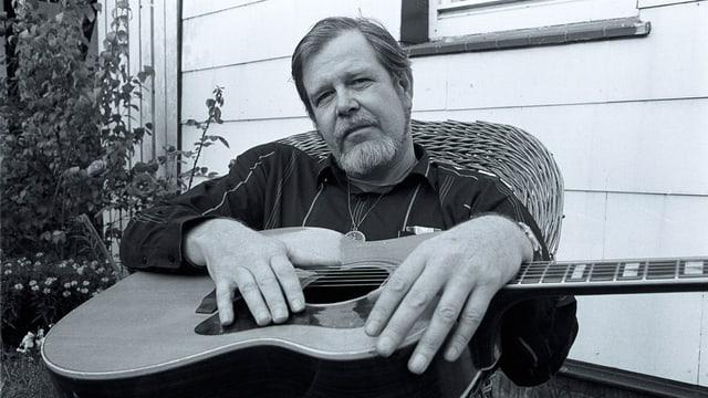 Ein Mann sitzt auf einem Korbsessel mit Gitarre auf dem Schoss.
