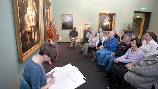 Menschen sitzen vor einem Bild, eine Frau notiert in einem grossen Buch, was sie sagen.
