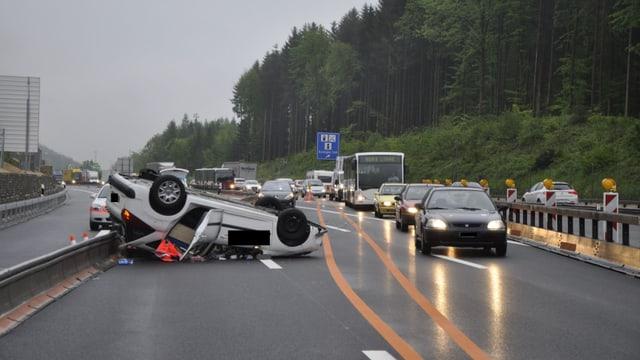 Ein Auto liegt auf der Autobahn auf dem Dach.