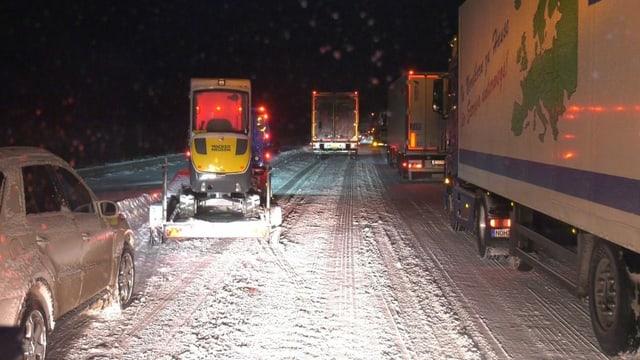 LKWs im Stau auf schneebedeckter Fahrbahn