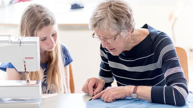 Ältere Frau hilft einem Mädchen beim Nähen.