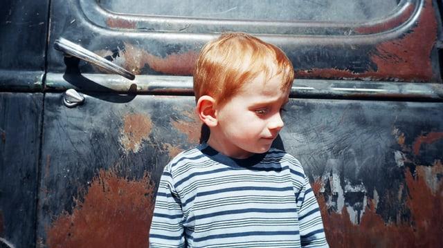 Kleiner Junge lehnt sich an ein verrostetes Auto.