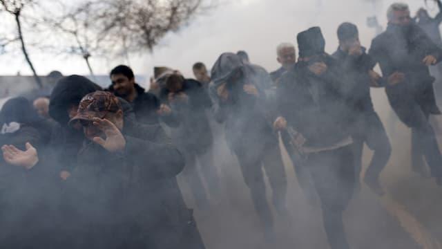 Ein paar Journalisten versuchen ihr Gesicht vor Tränengas zu schützen.