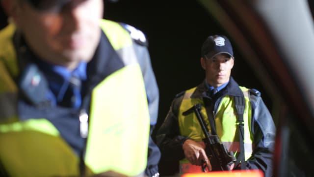 Zwei Kantonspolizisten kontrollieren ein Fahrzeug.