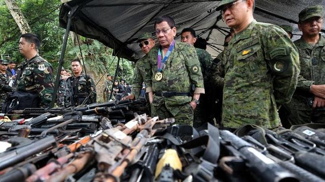Mehrere Männer in Uniform schauen sich Waffen auf Tischen an.