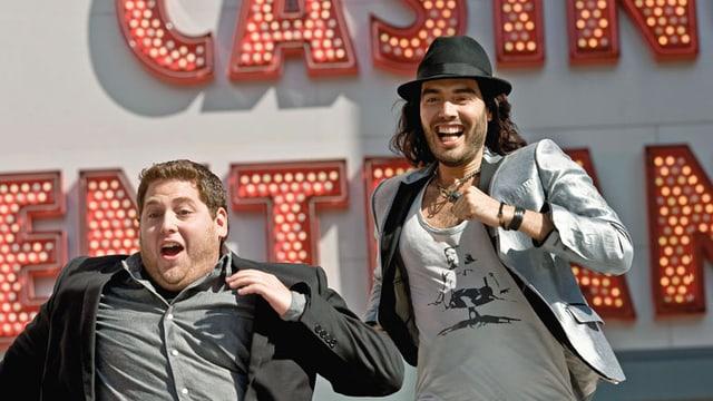 Zwei Männer rennen lachend irgendwohin.