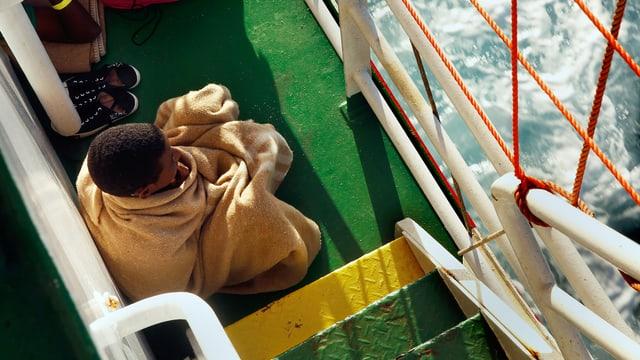 Mann in Decke gehült sitzt auf einem Schiff.