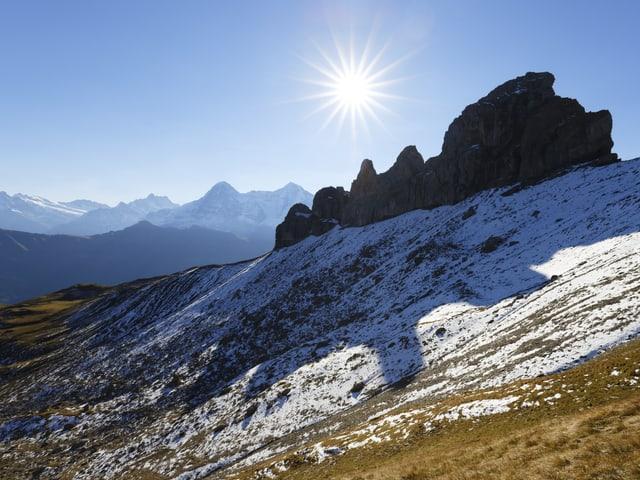 Blick auf eine Schneefläche mit einem Bergkamm dahinter. Die Sonne scheint vom blauen Himmel.