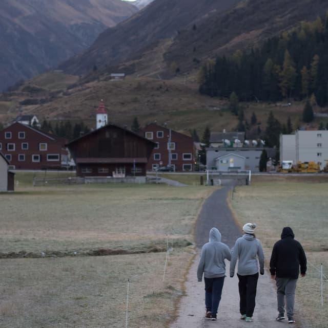Drei Personen gehen auf einer Strasse. Im Hintergrund ist Andermatt und die Berge zu sehen.