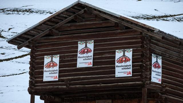 Ein Heuschober an einem verschneiten Hang: Vier SVP-Plakate gegen Masseneinwanderung kleben daran.