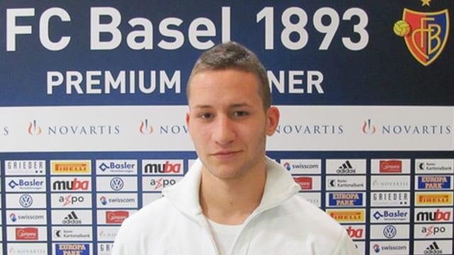 Vor der Werbewand des FC Basel posiert Simic in weissen Pullover. Er hat kurze, blonde Haare.