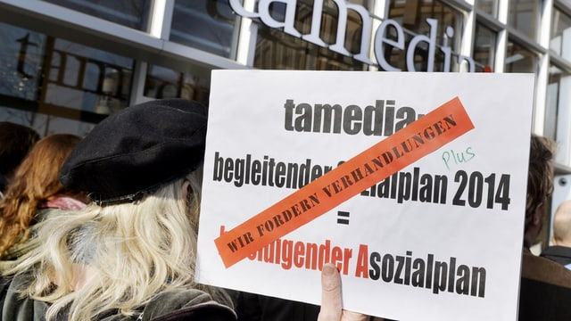 Protestiernde mit einem Schild, das Verhandlungen fordert, im Hintergrund die Fassade des Tamedia-Hauptsitzes in Zürich.