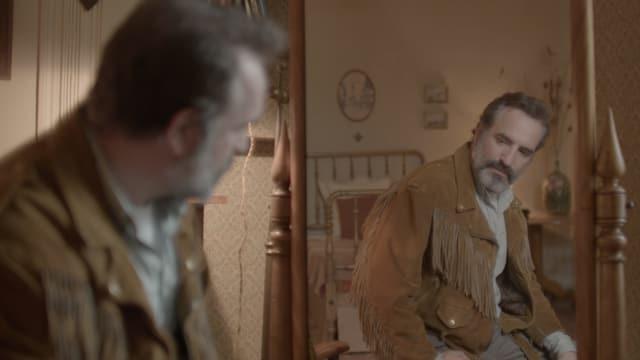 Ein Mann, der eine Lederjacke trägt, blickt sich im Spiegel an.