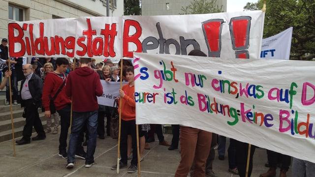 Menschen mit Plakaten, auf denen unter anderem steht: Bildung statt Beton