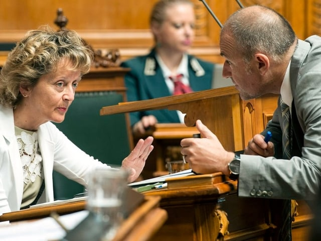 Mann spricht mit Frau im Nationalratssaal.