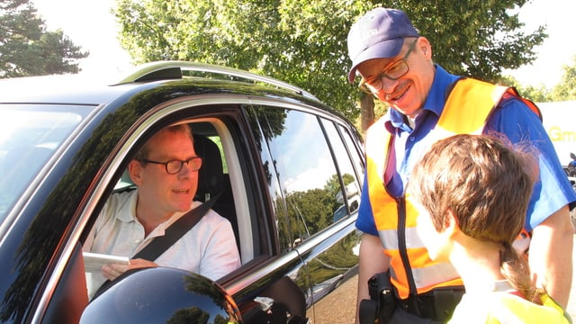 Ein Polizist und ein Schulkind überreichen einem Autofahrer eine Schokolade.