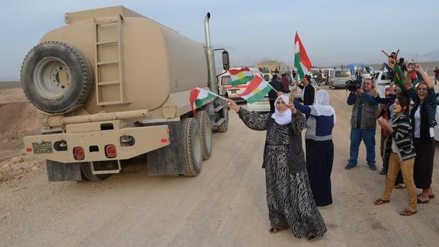 Kurden heissen die Lastwagenkolonne der Peschmerga willkommen und schwengen Fähnchen.