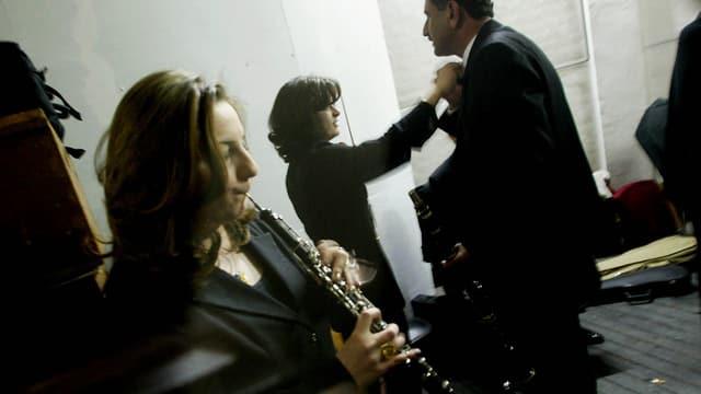 Im Probenraum des Irakischen Symphonie Orchesters: Im Vordergrund spielt eine Frau Klarinette, im Hintergrund wird einem Mann die Krawatte gebunden.