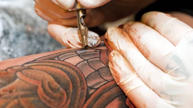 Ein Tätowierer sticht ein buntes Tattoo.