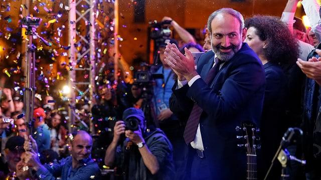 Paschinjan auf einer Bühne klatscht in die Hände, dazu fällt Glitter von oben herab.