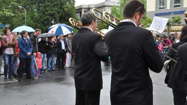 Foto da 3 musicants davos en che sunan en la plievgia. Davostier vesa ins aspectaturs en giaccas da plievgia e cun parisols.