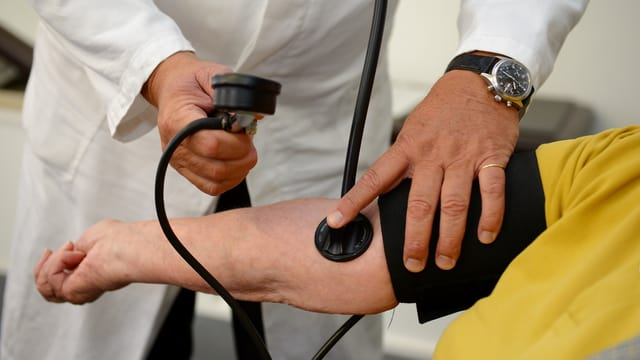 Arzt misst Blutdruck.