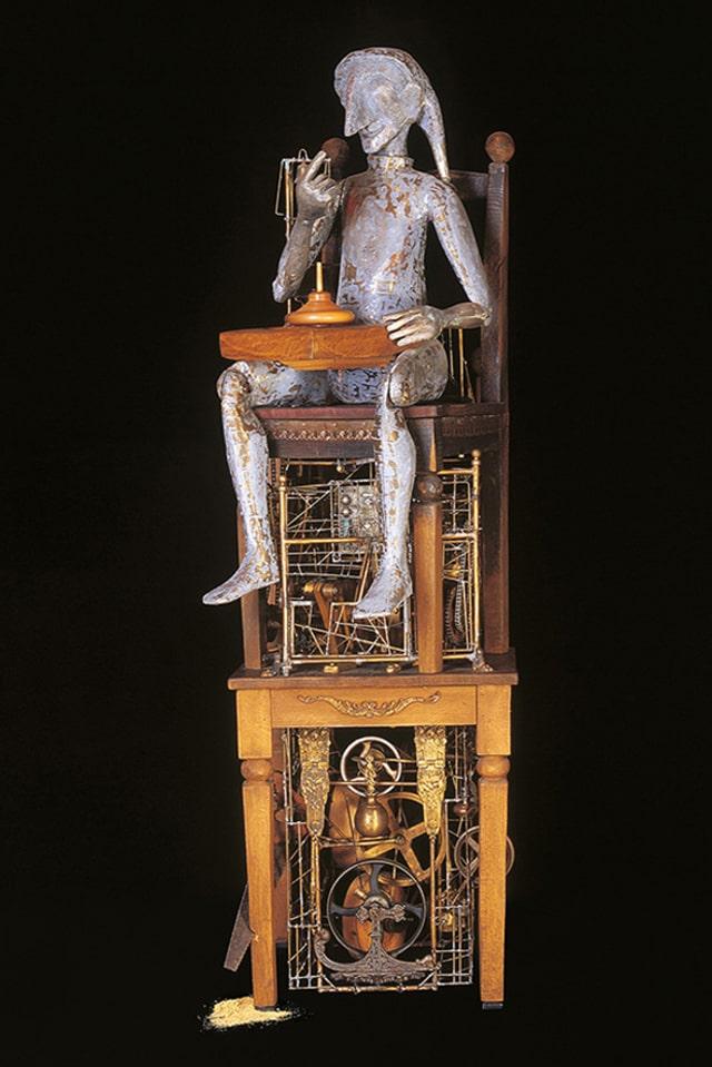 Skulptur einer Figur, die auf zwei Stühlen sitzt.