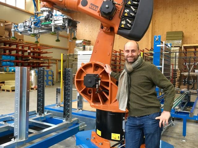 Ein Mann steht neben einem Roboterarm.