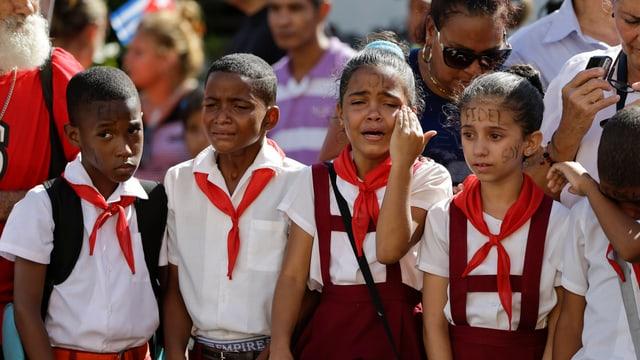 Kinder mit dem Namen Fidel Castros im Gesicht weinen