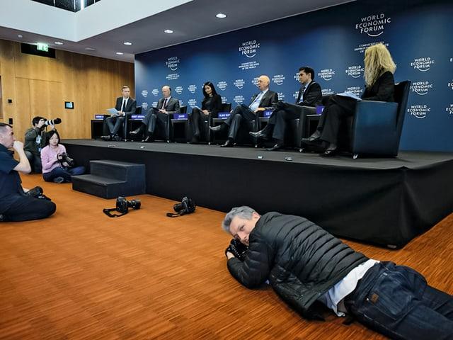 Ein Journalist liegt mit seiner Kamera vor einem Podiumsgespräch auf der Lauer.