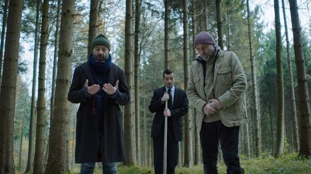 Drei Männer stehen im Wald