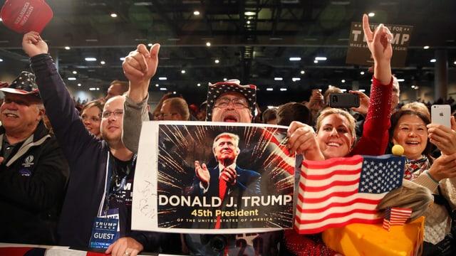 Jubelnde Menschen mit Amerkia-Flagge und Poster von Donald Trump.