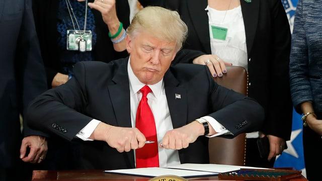 Donald Trump sesa vid ina maisa e suttascriva in decret per construir in mir al cunfin cun il Mexico.