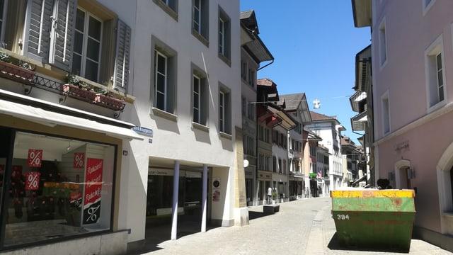 Altstadtgasse mit Häuser und Geschäften. Container auf Strasse.
