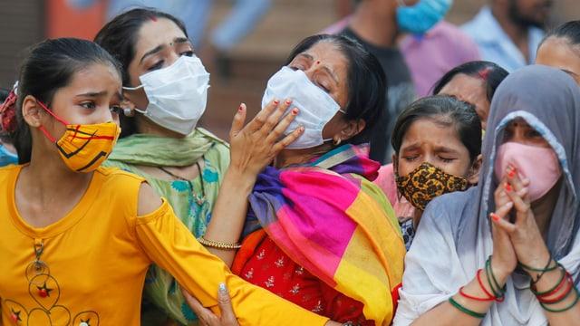 Angehörige trauern in Neu-Delhi um einen Mann, der an Covid-19 gestorben ist.