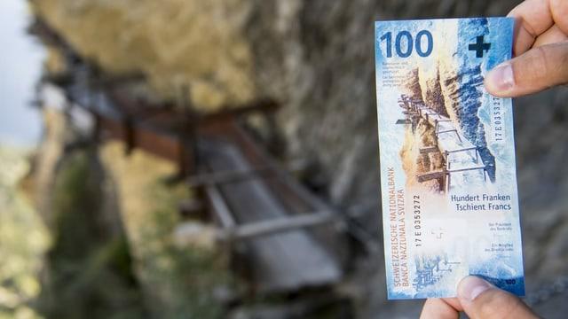 Dus mauns che tegnan ina bancnota da 100 francs.